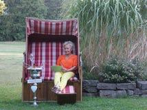 Sur un comprimé, la femme blonde dans la chaise de plage en osier couverte lit les salutations pour son anniversaire photos libres de droits