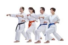 Sur un fond blanc les athlètes avec différentes couleurs des ceintures battent le bras de poinçon Images stock