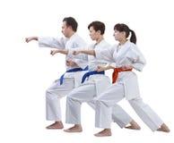 Sur un fond blanc les sportifs dans le karategi battent le bras de poinçon d'isolement Photographie stock