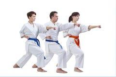 Sur un fond blanc trois les sportifs forment le bras de poinçon Images libres de droits
