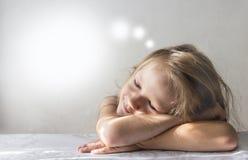 Sur un fond blanc une fille de rêve de sourire de sommeil se situe dans les rayons de l'espace de copie de matin du soleil photographie stock