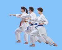Sur un fond bleu-clair les athlètes battent le bras de poinçon Photo stock