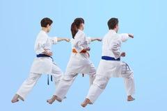 Sur un fond bleu-clair un homme et les femmes dans le karategi frappent le bras de poinçon Photo libre de droits