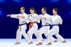Sur un fond bleu-foncé les athlètes adultes battent le bras de poinçon Photo stock