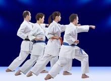Sur un fond bleu-foncé les athlètes battent le bras de poinçon Image libre de droits