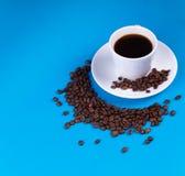 Sur un fond bleu, une tasse de café à côté de elle est remplie de grains de café sous forme de croissant image libre de droits