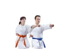 Sur un fond de blanc les athlètes adultes battent le bras de poinçon Image libre de droits