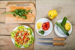 Sur un fond en bois il y a les couteaux, une planche à découper avec des plats de verts avec des légumes images libres de droits