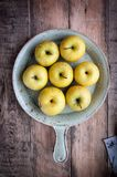Sur un fond en bois sur les pommes fraîches d'un plateau avec des gouttelettes d'eau Photo stock