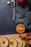 Sur un fond est un conseil avec des pommes coupées en tranches, une brindille d'afir-arbre et la moitié de l'orange Vue supérieur image stock