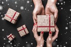 Sur un fond noir, les mains du ` un s d'homme portent un cadeau dans les mains d'une jeune dame, avec l'effet de flocon de neige Photographie stock libre de droits
