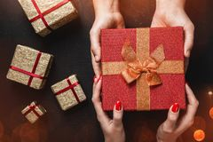 Sur un fond noir, les mains du ` un s d'homme portent un cadeau rouge dans les mains d'une jeune dame Photos libres de droits