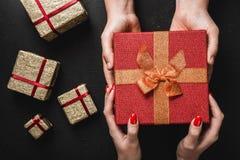 Sur un fond noir, les mains du ` un s d'homme portent un cadeau rouge dans les mains d'une jeune dame Carte de vacances Photos stock