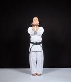 Sur un fond noir, un athlète forme des exercices formels de karaté Image libre de droits