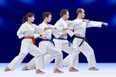 Sur un fond quatre bleu-foncé les athlètes adultes battent le bras de poinçon Photo libre de droits