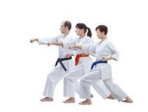 Sur un fond trois blancs les athlètes adultes battent le bras de poinçon d'isolement Images libres de droits