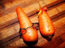 Sur un hachoir en bois les carottes sont un garçon et une fille Images libres de droits