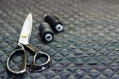 Sur un noir le tissu piqué, plan rapproché, se trouvent des ciseaux et filètent l'esprit Images stock