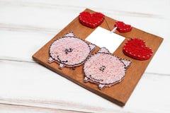 Sur un panneau en bois fond-fait main blanc en bois avec des images des coeurs et des porcs Au centre d'une feuille de papier iso images stock
