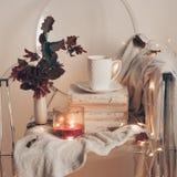 Sur une chaise transparente en plastique - couvre-lit chaud, une tasse de thé sur des livres et une bougie avec des feuilles d'au images stock