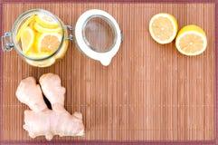 Sur une couverture de bambou pouvez avec les tranches de citron, le gingembre et deux moitiés de citron, vue supérieure Images stock