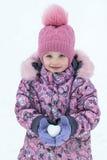 Sur une fille de jour du ` s d'hiver se tenant dans des mains lancez des boules de neige sous forme de Photo stock