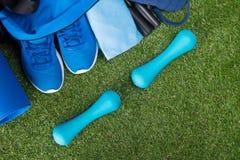 Sur une pelouse verte, un ensemble bleu de choses pour faire des sports, un sac avec des choses et des chaussures, et deux haltèr Images stock
