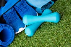 Sur une pelouse verte, un ensemble bleu de choses pour faire folâtre sur une couverture gymnastique, un sac avec des choses et de Images stock