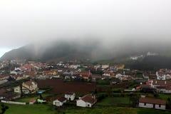 Sur une petite ville côtière des montagnes le brouillard descend Photographie stock