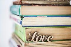 Sur une pile d'amour en bois de mot de vieux livres Photographie stock