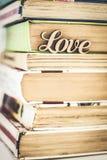 Sur une pile d'amour en bois de mot de vieux livres Photo stock