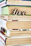 Sur une pile d'amour en bois de mot de vieux livres Photos libres de droits