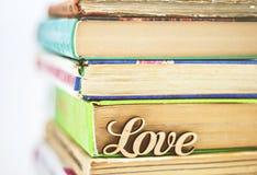 Sur une pile d'amour en bois de mot de vieux livres Images stock