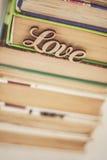 Sur une pile d'amour en bois de mot de vieux livres Image stock