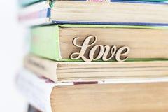 Sur une pile d'amour en bois de mot de vieux livres Photos stock