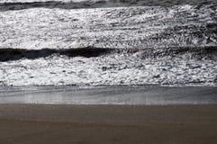 Sur une plage sablonneuse la vague roule la nuit Photos stock