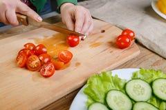 Sur une planche à découper, couteaux d'une femme le régime des tomates-cerises dans des tranches pour la salade végétale photo stock