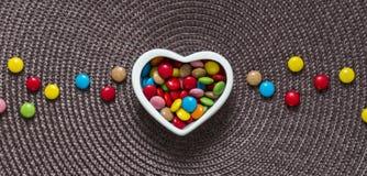 Sur une serviette au centre d'un vase avec la sucrerie colorée sous forme de coeur et de sucrerie de mensonge Photo libre de droits