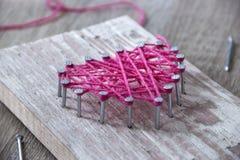 Sur une table en bois étendue les clous de marteau filetez le rose et le cadeau avec leurs propres mains le coeur du fil et des c Photo stock
