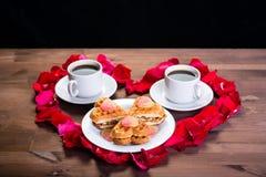 Sur une table en bois au coeur des pétales des roses il y a deux tasses de café et d'un plat avec des biscuits Copiez l'espace su Images stock