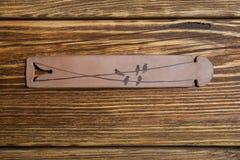 Sur une table en bois brune est un bracelet en cuir avec des oiseaux Photos stock