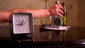 Sur une table en bois brune polie, avec une réflexion, il y a argent carré avec un cadran blanc, une horloge et un carnet banque de vidéos