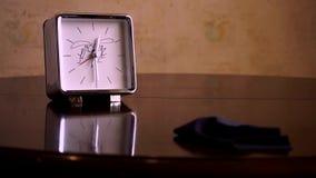 Sur une table en bois brune polie, avec une réflexion, il y a d'argent carré avec un cadran blanc, une horloge avec des jambes E banque de vidéos