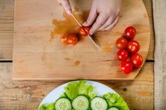 Sur une table en bois, couteaux d'une femme un régime des tomates image stock