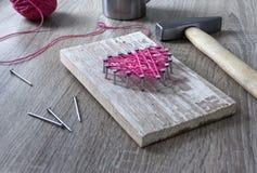 Sur une table en bois se trouve un marteau d'un clou d'un rose de fil et d'un cadeau avec vos mains un coeur des fils et cloue un Photo stock