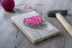 Sur une table en bois se trouve un marteau d'un clou d'un rose de fil et d'un cadeau avec vos mains un coeur des fils et des clou Images stock