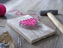 Sur une table en bois se trouve un marteau d'un clou d'un rose de fil et d'un cadeau avec vos mains un coeur des fils et des clou Image libre de droits