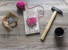 Sur une table en bois se trouve un marteau d'un clou d'un rose de fil et d'un cadeau avec vos mains un coeur des fils et de la ta Photo stock