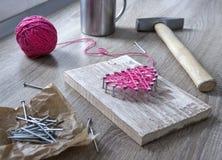 Sur une table en bois se trouve un marteau d'un clou d'un rose de fil et d'un cadeau avec votre coeur de mains des fils et cloue  Photos stock