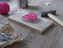 Sur une table en bois se trouve un marteau d'un clou d'un rose de fil et d'un cadeau avec votre coeur de mains des fils et cloue  Photographie stock libre de droits